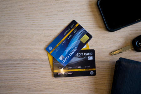 Closeup of credit card with car keys, phone and wallet on wood table. Travel holiday concept Banco de Imagens