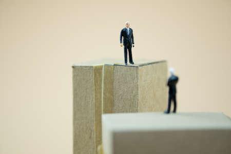 Miniaturleute: Geschäftsmann, der auf braunem Kasten steht und mit Partnerschaft spricht. Konzept der Geschäftsverhandlungen Standard-Bild
