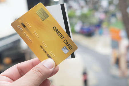 Close up of credit card with paper cinema ticket in hands. Concept of pay by credit card