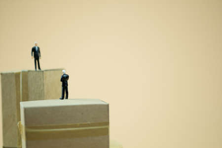 Miniature people: Businessman standing on brown box and talk with partnership. Concept of business negotiation