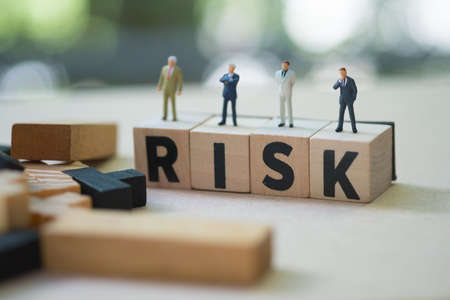 Miniature people group of businessmen stand on cube word with risk. Risk analysis for investment. The concept business risk assessment or management concept