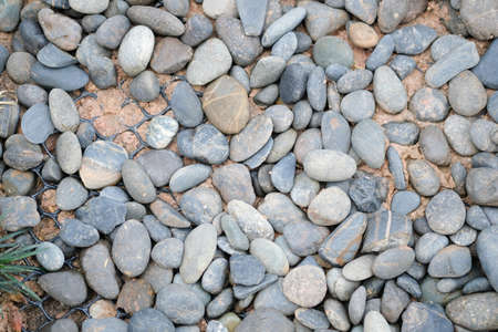 Abstract nature pebbles background. Blue pebbles texture. Various turquoise sea pebbles on the beach lit by sunlight
