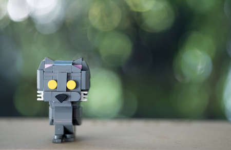 Cute of plastic toy black cat standing on a wood table