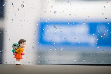 Happy miniature girl piggybacking adorable little sister against rain water drops on windows glass background. childhood concept