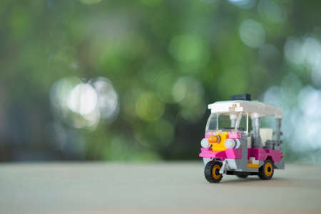 Toy miniature tuk-tuk or tricycle in Thailand with nature background. Travel in Thailand