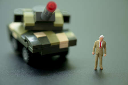 Miniature people stand front of  miniature military army vehicle tank