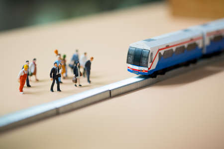 Close up miniature people waiting train at early morning rush hours, busy modern life concept. Thailand public transportation concept