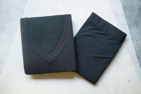 Pants and t-shirt black folded for winter season. Technology from japan that call Heattech can help to generate heat and keep body warm