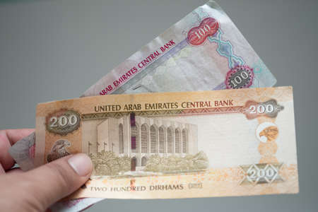 A close up image of dirham banknote from the United Arab Emirates in man hand Stock Photo