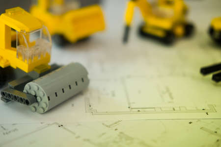 Yellow toys transport construction on blueprints or  architectural project, construction plan concept