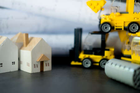Miniature wood home with toys transport construction. Construction site concept Stock Photo
