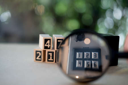 Magnifying glass on the number pad lock on safe box. Concept of security and protection Stock Photo