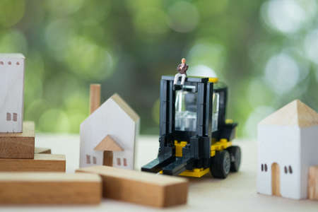 Miniature banker with yellow forklift. Concept of risks, lost property, seized, mortgage Banco de Imagens