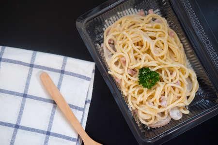 Spaghetti carbonara with bacon and ham in transparent plastic box.