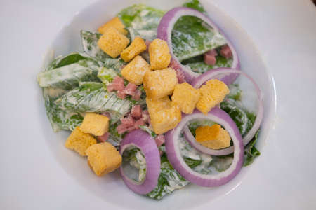 Fresh caesar salad in white dish. Healthy food concept