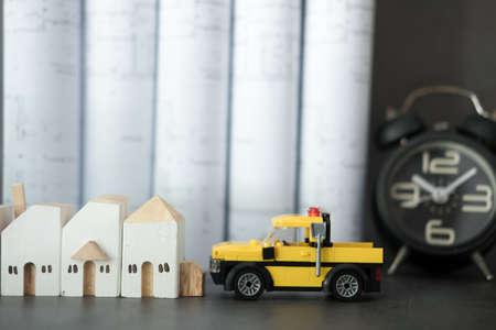 Casa in legno in miniatura e camion giallo con sfondo di orologio e piano di costruzione. Concetto di tempo per il cantiere Archivio Fotografico