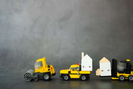 A set of yellow construction car transports wooden houses. Machines for building services Stock Photo