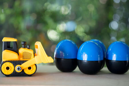 Toy bulldozer carry egg toys open inside mini toy to surprise. Concept of delivering toy for fun