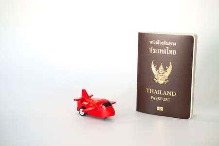 A passport for Thai citizen and a mini red airplane toy on white background Stock fotó