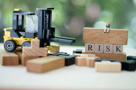 Miniature businessman sitting on wooden blocks and alphabets word RISK. Risk assessment for business or investment