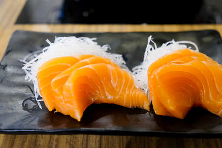 Fresh orange sliced salmon or Salmon Sashimi on black plate