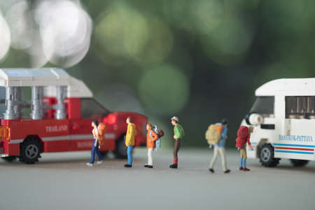Close up of group of traveler miniature with backpack go to van and minibus