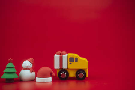 Toy of christmas tree , gift box on truck, snowman and Santa Claus hat on red background with copy space. Start of season. Christmas celebration concept Stock Photo