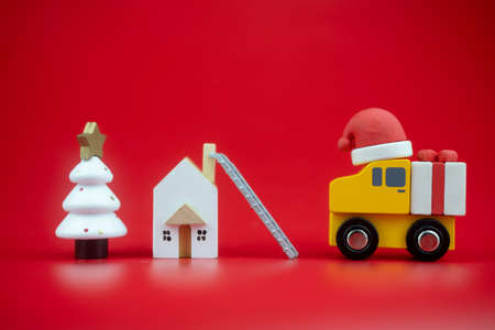 Yellow toy truck carry present sent to kid at home by santa claus on red background. Holiday delivery.