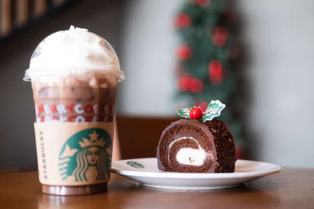Bangkok, Thailand - December 8, 2019 : Iced mocha with whipped cream and Christmas log cake the product from Starbucks coffee shop in season Christmas. Famous coffee brand franchise originated in USA Imagens
