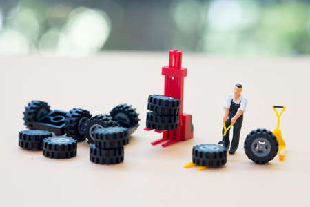 Miniature people : Handsome mechanic in uniform is examining a tire working in auto service. Concept of tire at the repair garage replacement