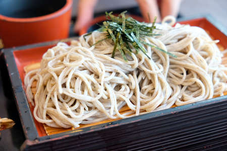 Cold soba (buckwheat noodles) served on a wickerwork platter and eaten after being dipped in a cold sauce Standard-Bild