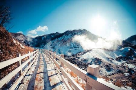 The wooden walking footpath trail bring to hot springs. Beautiful landscape view of Noboribetsu Jigokudani or Hell Valley in winter seasonal at Hokkaido, Japan. 写真素材