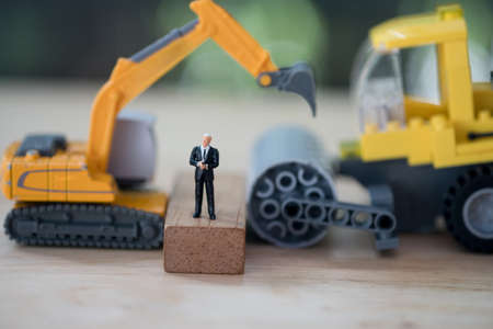 Miniature people: businessman standing in front of yellow toy excavator. Investment analysis investment in movable property.