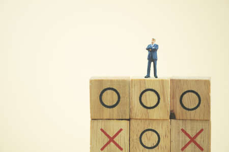 Business direction and planning concept. Businessman miniature standing and thinking on o x board games. (Tic Tac Toe). Business direction and planning concept 写真素材