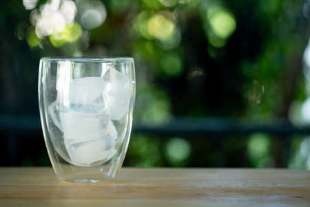 Ice tube in empty glass on wood table