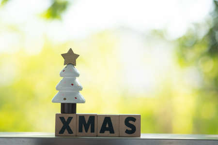 Miniature of Christmas tree on letters spelling XMAS. Festive Christmas concept