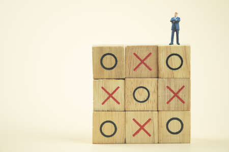 Business direction and planning concept. Businessman miniature standing and thinking on o x board games. (Tic Tac Toe). Business direction and planning concept