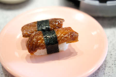 Unagi eel sushi on pink dish. Japanese food traditional cuisine