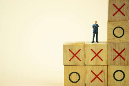Businessman miniature standing and thinking on o x board games. (Tic Tac Toe). Business direction and planning concept