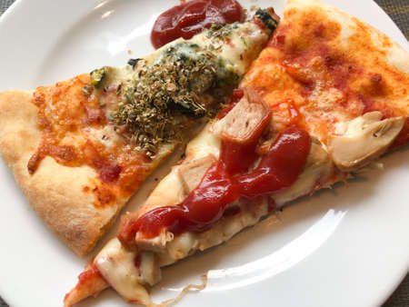 Two piece of pizza with tomato on white dish Banque d'images