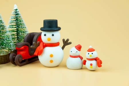 Cute snowmen with sleigh on yellow background