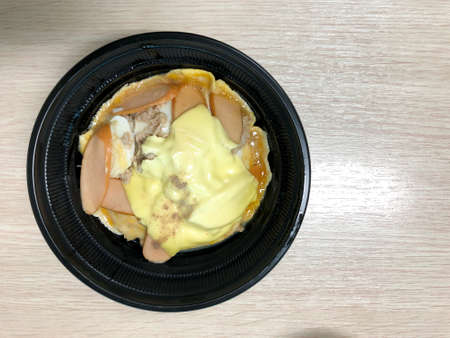 Creamy omelet with hot dog, cheese and minced pork on top rice in black bowl