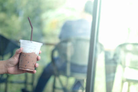 Glass of iced mocha with milk froth in hand