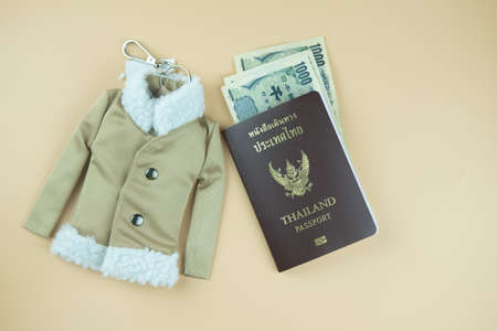 Thailand passport and Japan money with winter coat key ring for travel in Japan. Tourism and travel in Japan concept.