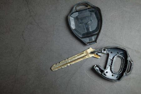 Close up dirty broken or damaged car remote key on black background Banco de Imagens