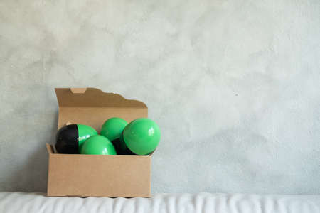 Green and black plastic toy surprise egg in brown box. Toy inside egg