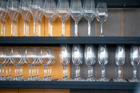 Empty wine glasses in a row on a shelf in the kitchen.