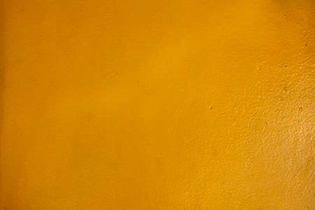 The surface of the concrete wall that is beautifully painted in the yellow of the building Stock Photo