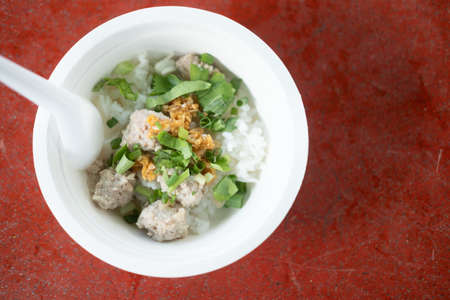 Close up a boiled rice with minced pork in paper bowl
