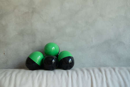 Plastic toy in the shape of a green-black egg put on sofa. Toy it random inside